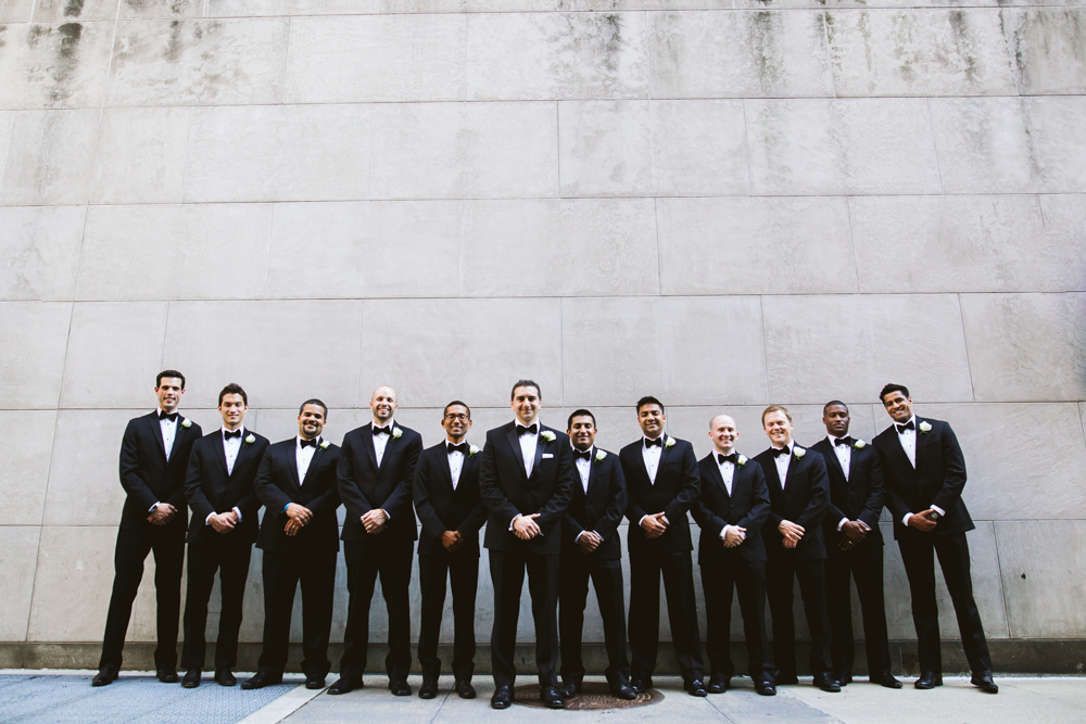 Groomsmen photo against wall